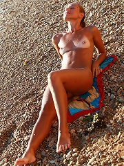 Skinny small breasted girl tanning on the beach