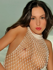 Hot Guinevere seductive in her fishnet dress playing her pussy with her fingers
